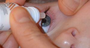 закапывает глазные капли ребенку