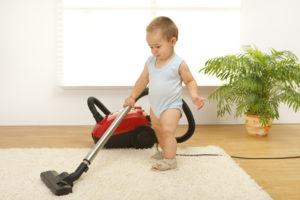 малыш делает уборку комнаты и пылесосит ковер